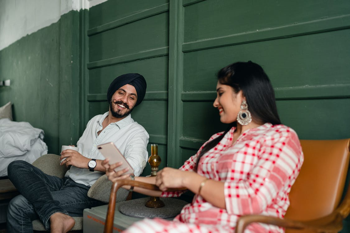 Happy married couple using smartphone and discussing funny Internet post