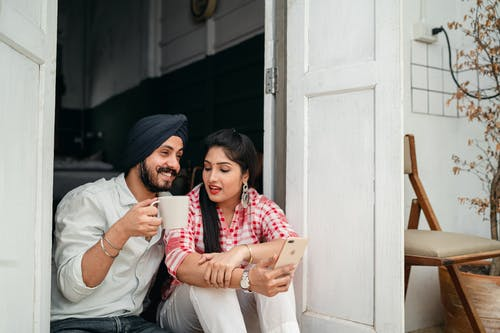 Young couple chatting while sitting in doorway of veranda