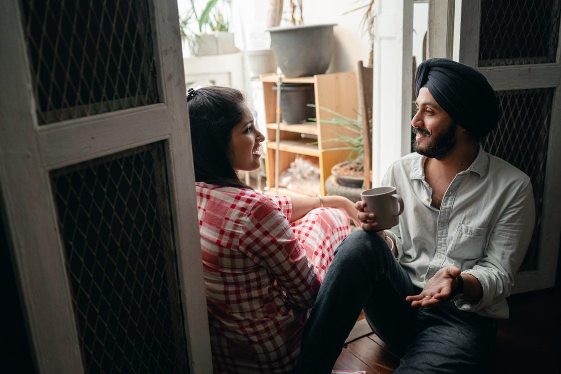 Positive young Indian spouses having lively conversation and drinking coffee while relaxing on threshold of sunlit enclosed balcony