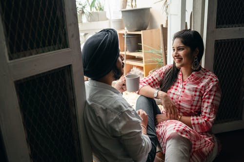 Indian couple chatting while enjoying weekend at home