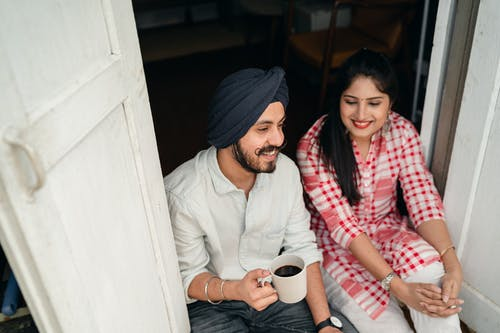 From above of smiling young Indian man with black coffee and woman in bright checkered shirt having pleasant conversation while sitting at threshold