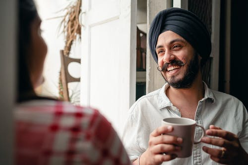 Cheerful man with coffee laughing together with woman