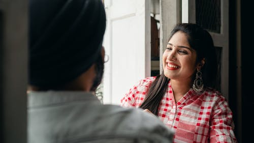 Cheerful young lady talking to faceless man and laughing