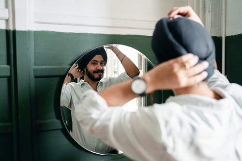 Back view of satisfied young Indian male hipster with twisted mustache wearing denim shirt and turban standing against mirror on wall while taking care about appearance