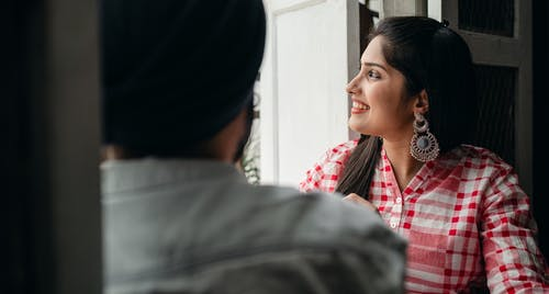 Cheerful Indian wife spending time with crop husband at home