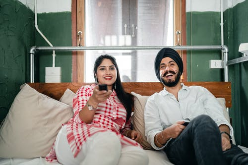 Cheerful wife with bindi on forehead wearing plaid tunic with white trousers using TV remote control for channel switching while lying on bed with laughing Sikh husband in turban with stylish beard and twisted mustache