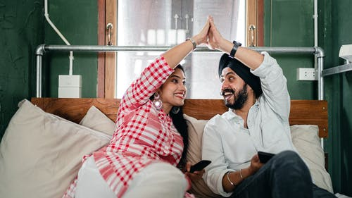 Young ethnic man and woman in casual outfit sitting in modern bedroom and enjoying weekend while doing high five on comfortable sofa