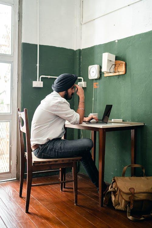 Pensive ethnic man typing on laptop in modern workspace