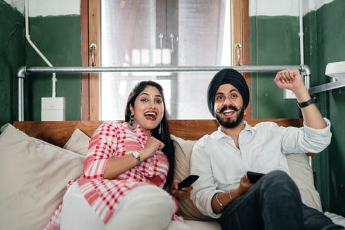 Young ethnic couple with remote control lounging in bedroom