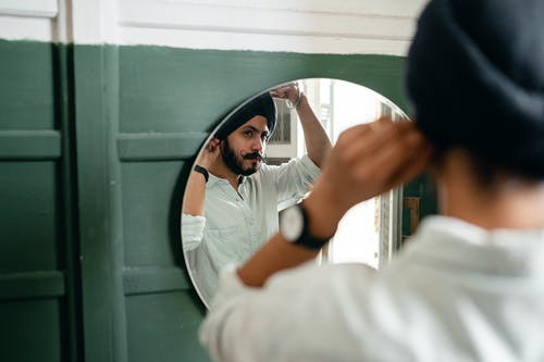 Focused ethnic man showing turban in mirror at home