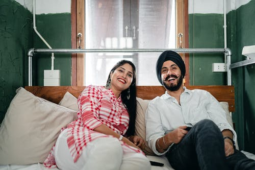 Happy ethnic couple relaxing on sofa in living room