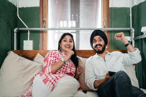 Delighted ethnic couple resting together on couch at home