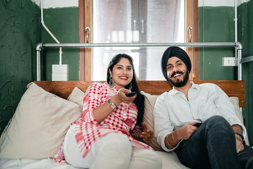Cheerful Indian man and woman in casual wear resting in modern bedroom and using remote control while watching comedy film together