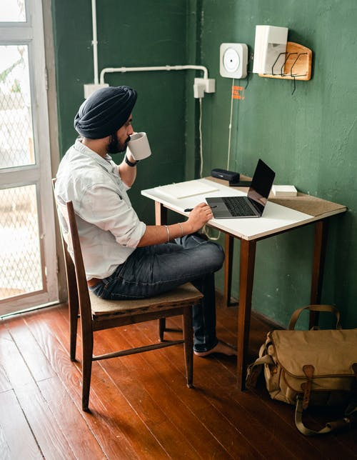 Ethnic man using laptop and drinking tea