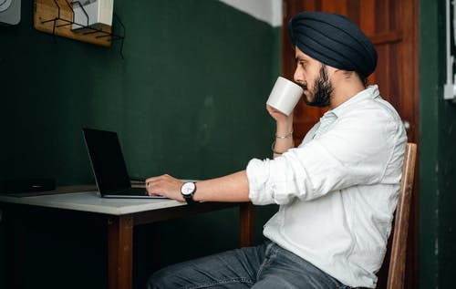 Side view of young bearded Indian male in casual wear and turban drinking coffee while working remotely on laptop