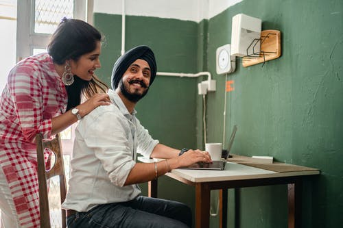 Smiling young Indian woman in casual clothes caring for positive husband working on laptop from home