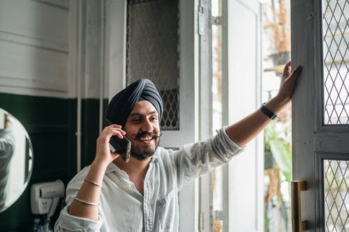 Young smiling Sikh man speaking on smartphone at home