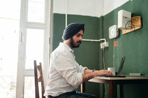 Side view low angle of focused young Sikh male in formal wear and turban sitting at table and working on laptop during remote job