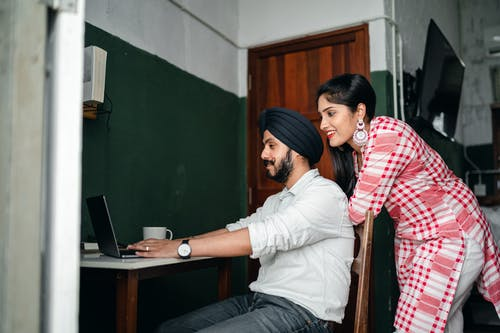 Side view of positive young Sikh man in shirt and turban working on laptop at home while wife leaning on chair behind