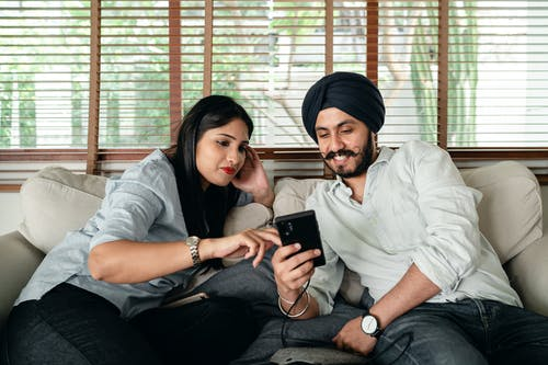 Happy Indian couple using smartphone together
