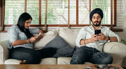 Young serious bearded man in turban and woman in casual outfit sitting on comfortable couch and messaging on smartphones