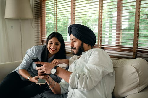 Young bearded Indian man in casual clothes and turban showing photos on smartphone to cheerful woman while resting on sofa