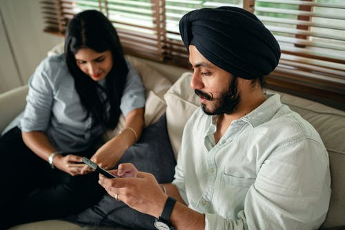 Young Indian couple surfing internet on smartphones during weekend