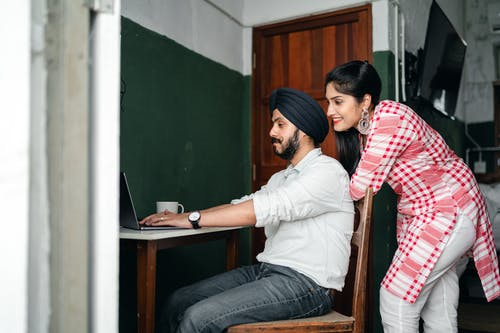 Young Indian spouses browsing netbook during online work