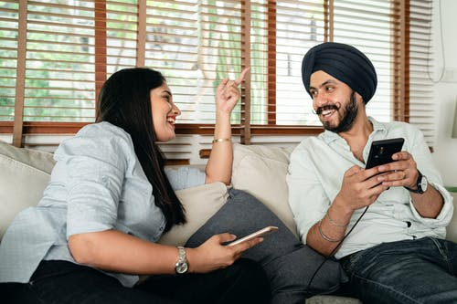 Cheerful young Indian couple in casual outfits with smartphone laughing and looking at each other on comfortable sofa during weekend