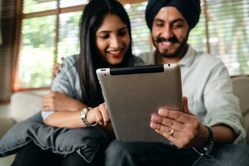 Joyful young Indian couple watching video on tablet and having fun