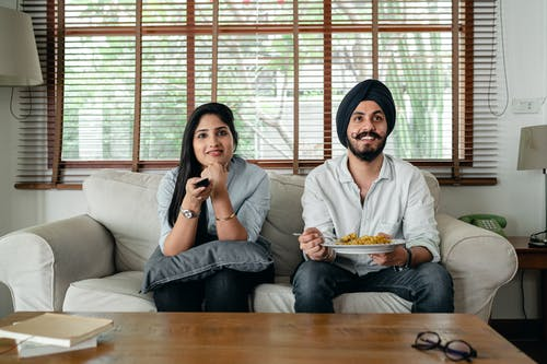 Smiling ethnic couple sitting on sofa and watching movie