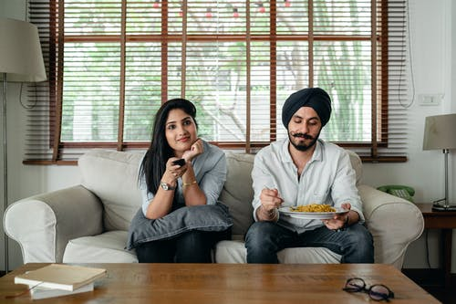 Pensive Indian male having meal on sofa while woman female in casual clothes sitting near and switching TV channels