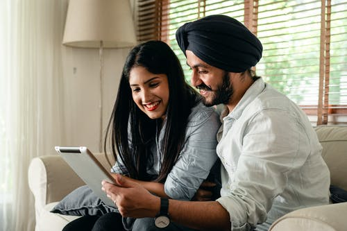 Calm ethnic couple browsing tablet and sitting in living room