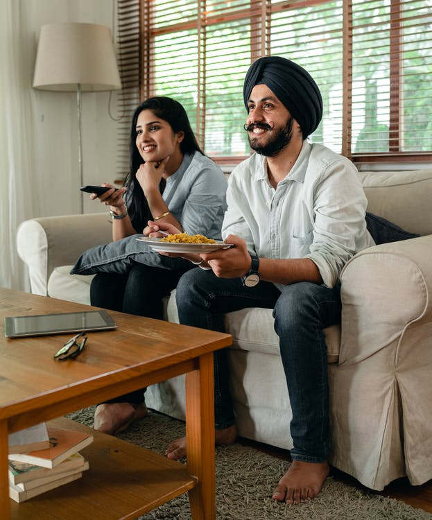 Happy Indian female and bearded male in casual clothes sitting on sofa in living room and smiling while watching tv