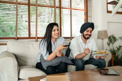 Happy ethnic male with plate of food and female with remote control sitting on couch in living room while watching movie