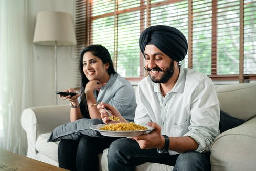 Delighted ethnic couple enjoying time at home and watching TV together