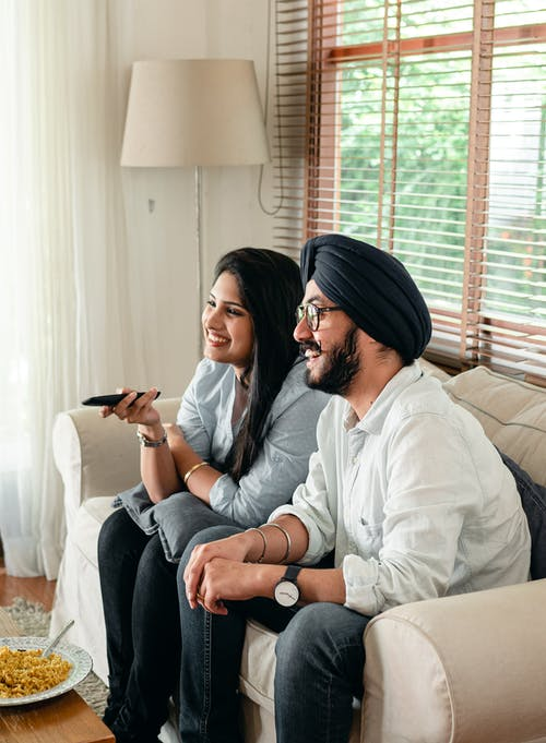 Side view of cheerful Indian male in eyeglasses sitting with female with remote control and sitting on couch in living room while watching movie