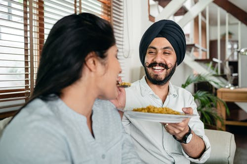 Positive ethnic man feeding woman while sitting on sofa