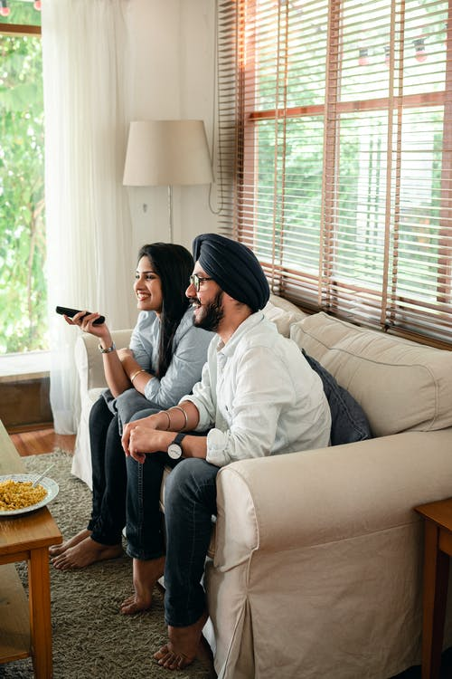 Happy Indian wife and husband in traditional turban resting on sofa and watching television