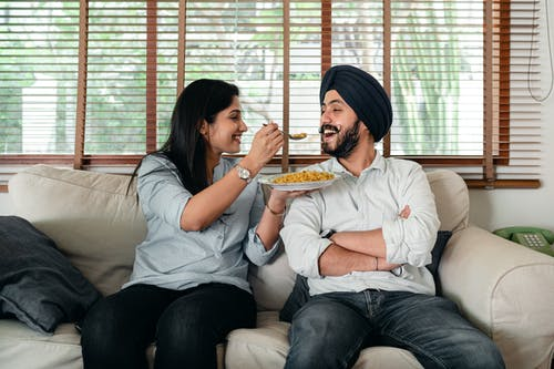 Positive Indian female in casual wear sitting on sofa in living room and feeding bearded male in turban