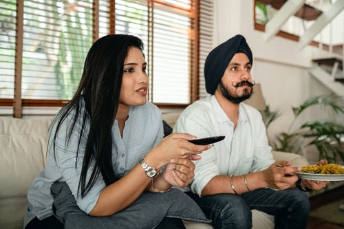 Serious ethnic couple watching movie on sofa
