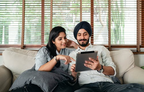 Content Indian woman and man in turban resting on cozy couch in living room and sharing tablet