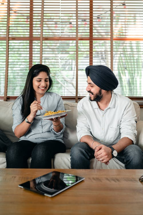 Cheerful young Indian couple having lunch together on couch