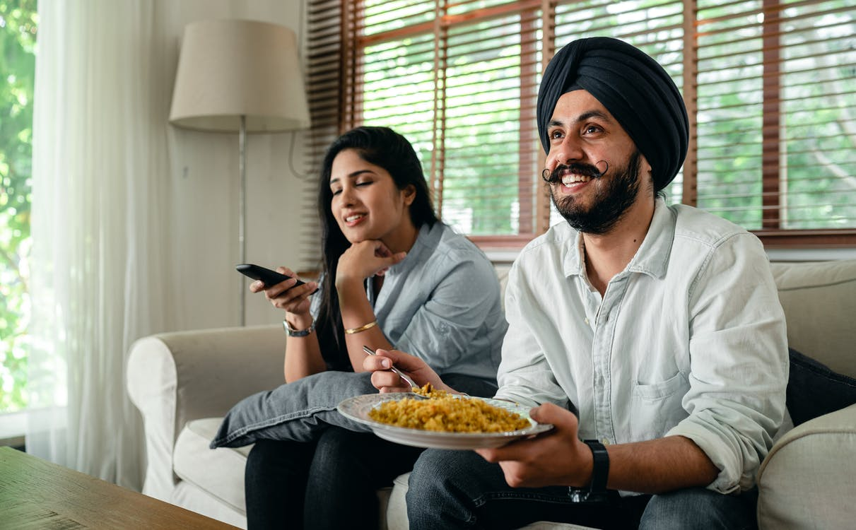Positive young bearded man in casual wear and turban eating traditional saffron rice on sofa while wife switching channels on TV with remote controller