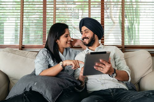 Smiling young Indian couple watching movie on tablet sitting on soft couch