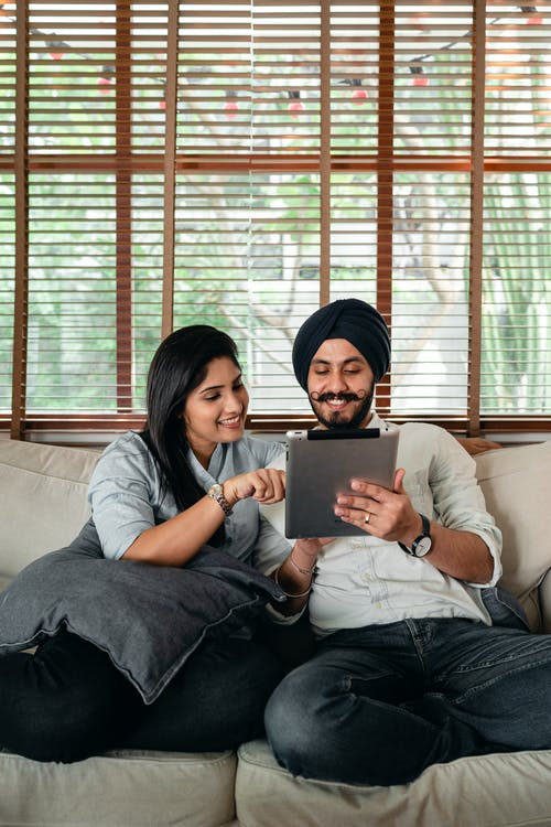 Happy Indian couple spending weekend together on couch with tablet