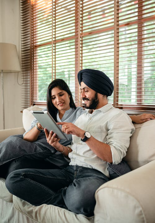 Optimistic young Indian couple browsing tablet on couch
