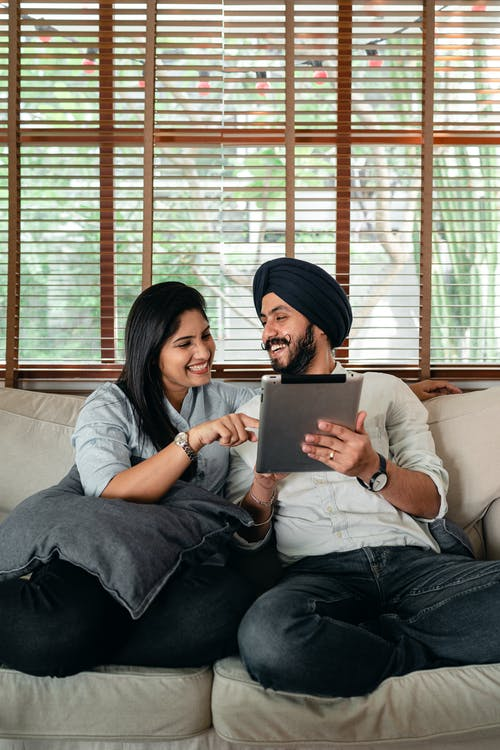 Joyful young Indian couple having fun while browsing tablet on couch
