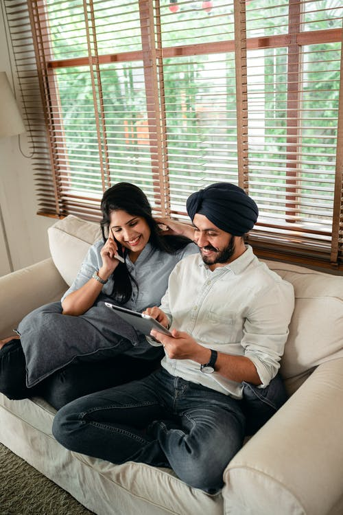 Young Indian couple using tablet and having phone conversation on couch