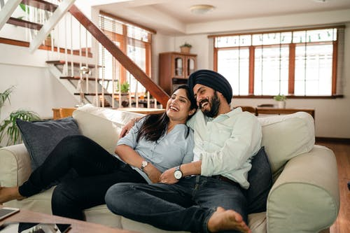 Happy young Indian couple laughing and cuddling while relaxing on couch